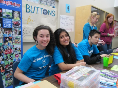 Palmer volunteers Maria, Neha and Henry take a shift at the products table.